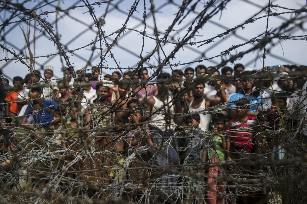In this file photo taken on April 25, 2018, taken from Maungdaw district, Myanmar's Rakhine state on April 25, 2018 shows Rohingya refugees gathering behind a barbed-wire fence in a temporary settlement setup in a