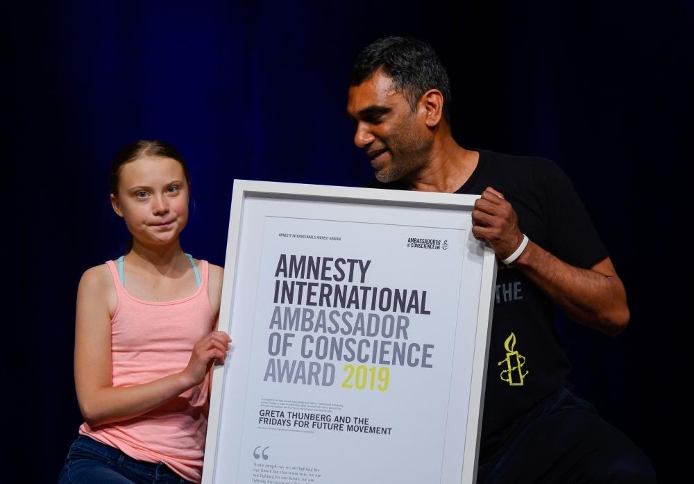 Swedish climate activist Greta Thunberg poses with Amnesty International Secretary General Kumi Naidoo after she received Amnesty International's Ambassador of Conscience award at George Washington University in Washington, DC on Monday. -AFP