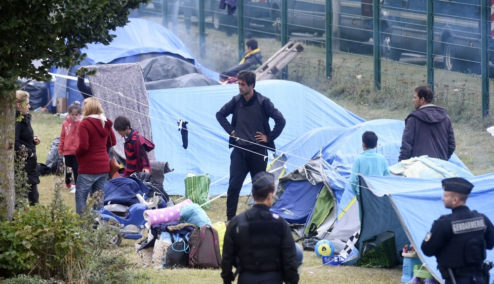 People leave the Grande Synthe migrant camp during its evacuation by French gendarmes on Tuesday in  Grande-Synthe, northern France. -AFP