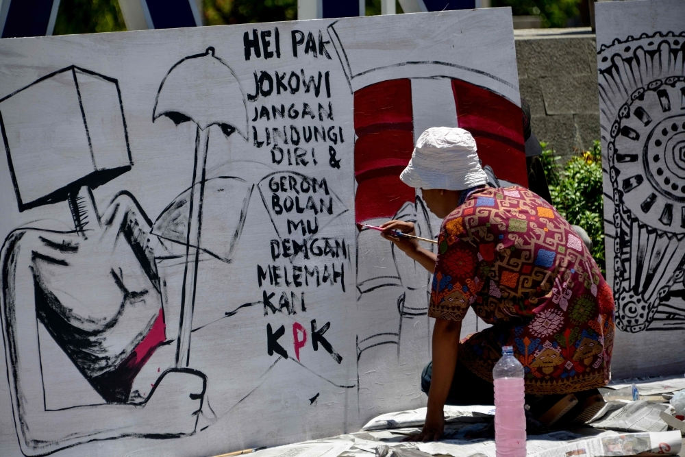 An Indonesian artist paints a protest board during a demonstration against the Corruption Eradication Commission's (KPK) law revision in Banda Aceh on Tuesday. -Reuters