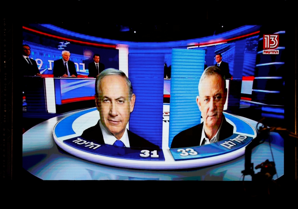 The results of the exit polls are shown on a screen at Benny Gantz's Blue and White party headquarters, following Israel's parliamentary election, in Tel Aviv, Israel, on Tuesday. — Reuters