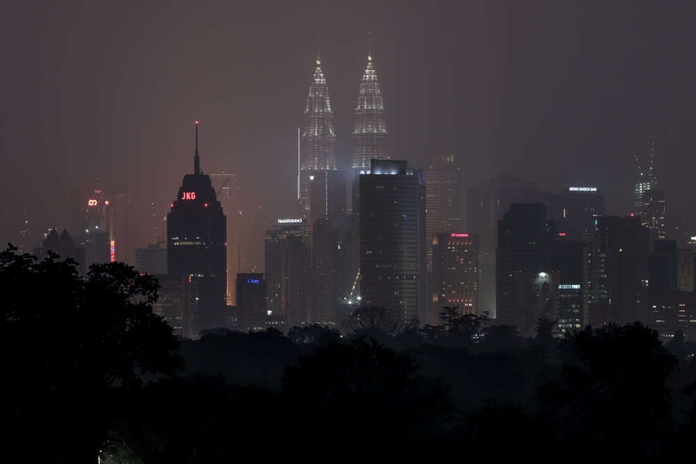 Malaysia's capital skyline with the Petronas Twin Towers (L) and Kuala Lumpur Tower (R) landmarks is blanketed by haze in Kuala Lumpur on Wednesday. Toxic haze from Indonesian forest fires closed thousands of schools across the country and in neighboring Malaysia, while air quality worsened in Singapore just days before the city's Formula One motor race. — AFP