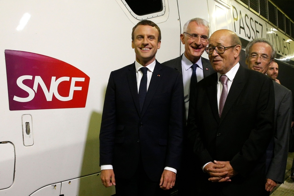 In this file photo taken on July 1, 2017, France's President Emmanuel Macron (L), flanked by French national state-owned railway company SNCF CEO Guillaume Pepy (2-L), French Foreign Affairs Minister Jean-Yves Le Drian (2-R) and chairman of the Supervisory Board Frederic Saint-Geours (R), poses next to a train for one of two new TGV (High Speed Train) lines at the Montparnasse train station in Paris. — AFP