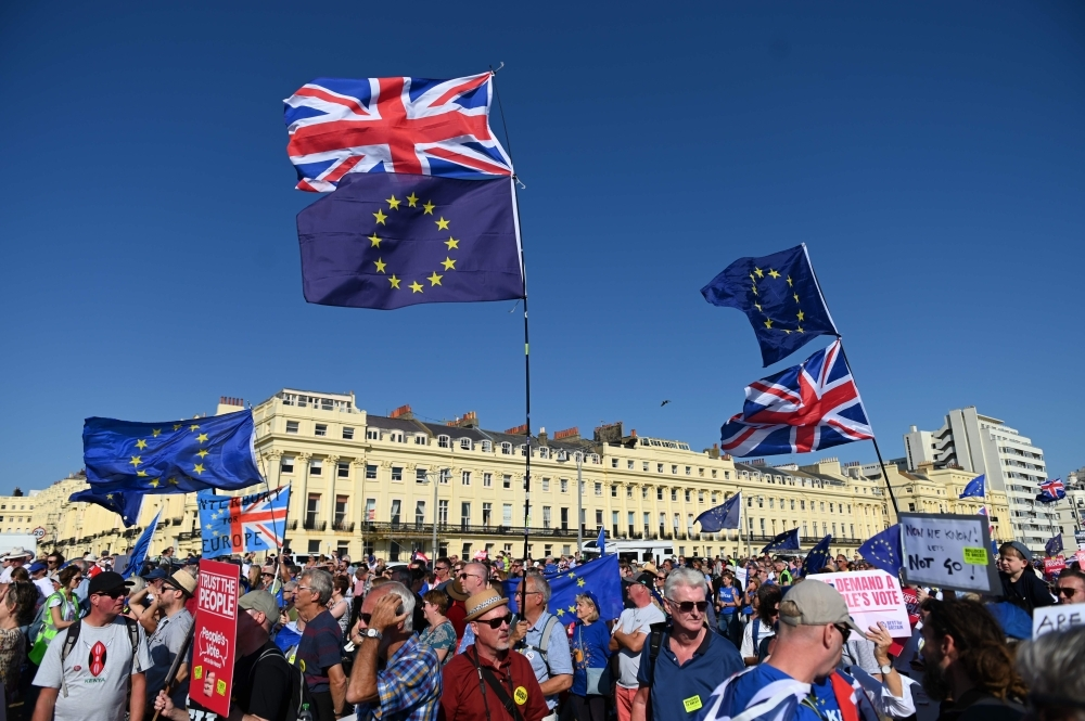 Protesters hold placards and wave EU and Union flags as they gather for a march and rally organised by