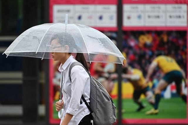 A woman walks past a poster advertising the Japan 2019 Rugby World Cup, while holding an umbrella in Oita on Sunday. -AFP