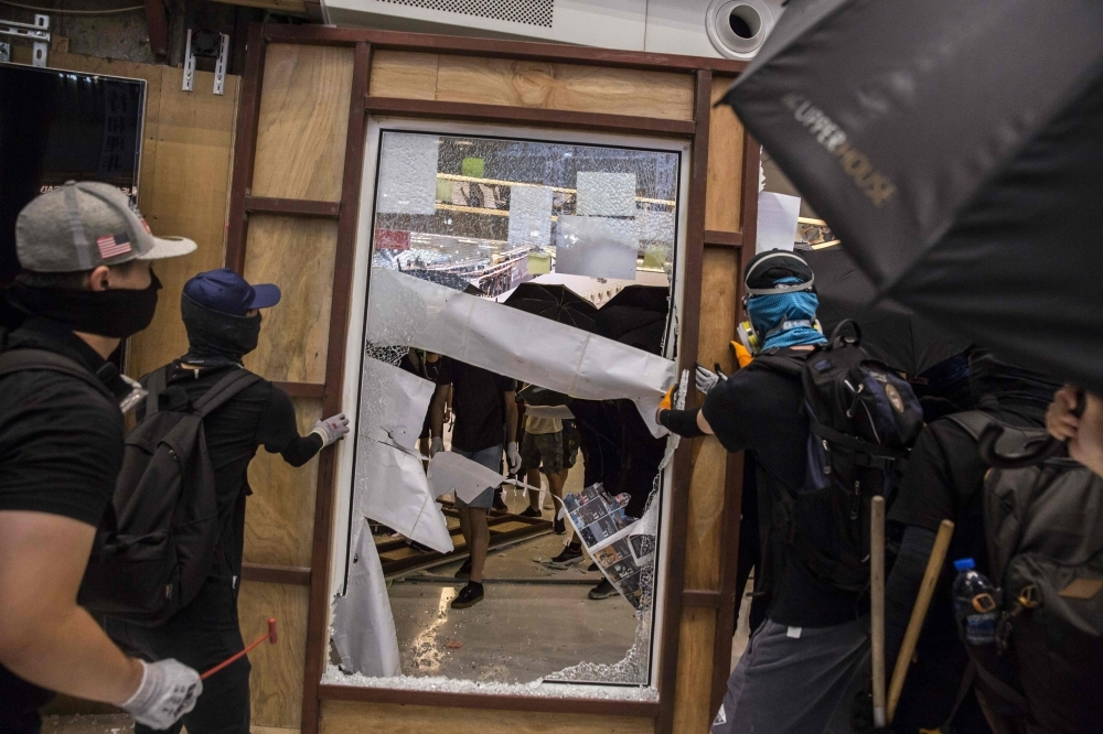 Pro-democracy protesters vandalize items at the New Town Plaza shopping mall in Hong Kong's Sha Tin district on Sunday. -AFP