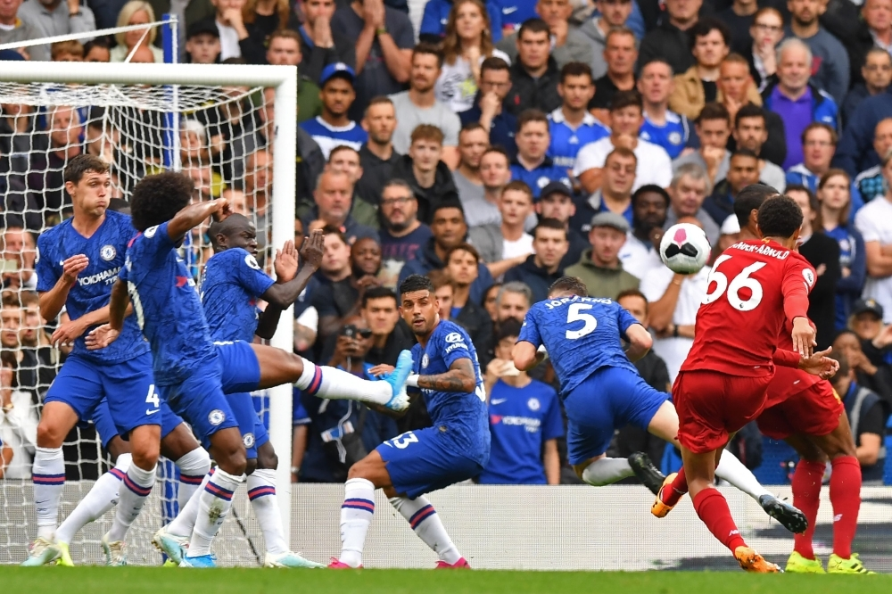 Liverpool's English defender Trent Alexander-Arnold (R) shoots to score the opening goal during the English Premier League football match between Chelsea and Liverpool at Stamford Bridge in London, on Sunday. — AFP