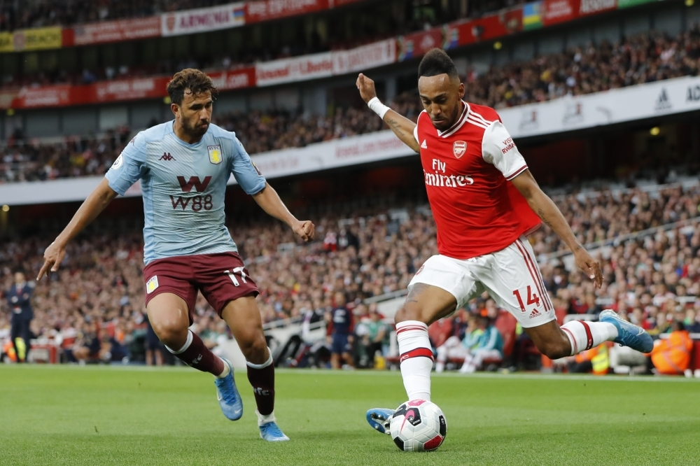 Arsenal's Gabonese striker Pierre-Emerick Aubameyang (R) crosses the ball during the English Premier League football match between Arsenal and Aston Villa at the Emirates Stadium in London, on Sunday. — AFP