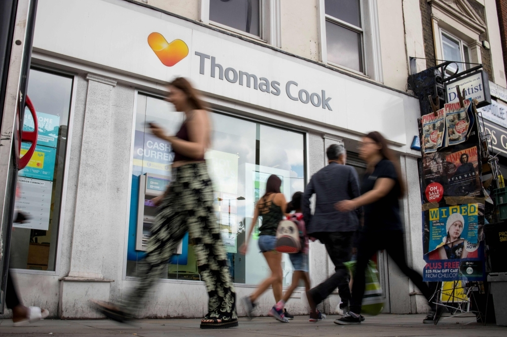 In this file photo taken on July 12, 2019, pedestrians walk past a branch of a Thomas Cook travel agent's shop in London. Thomas Cook's 178-year existence was hanging by a thread on Sunday after the iconic British travel firm struggled to find further private investment and is now relying on an unlikely government bailout. — AFP