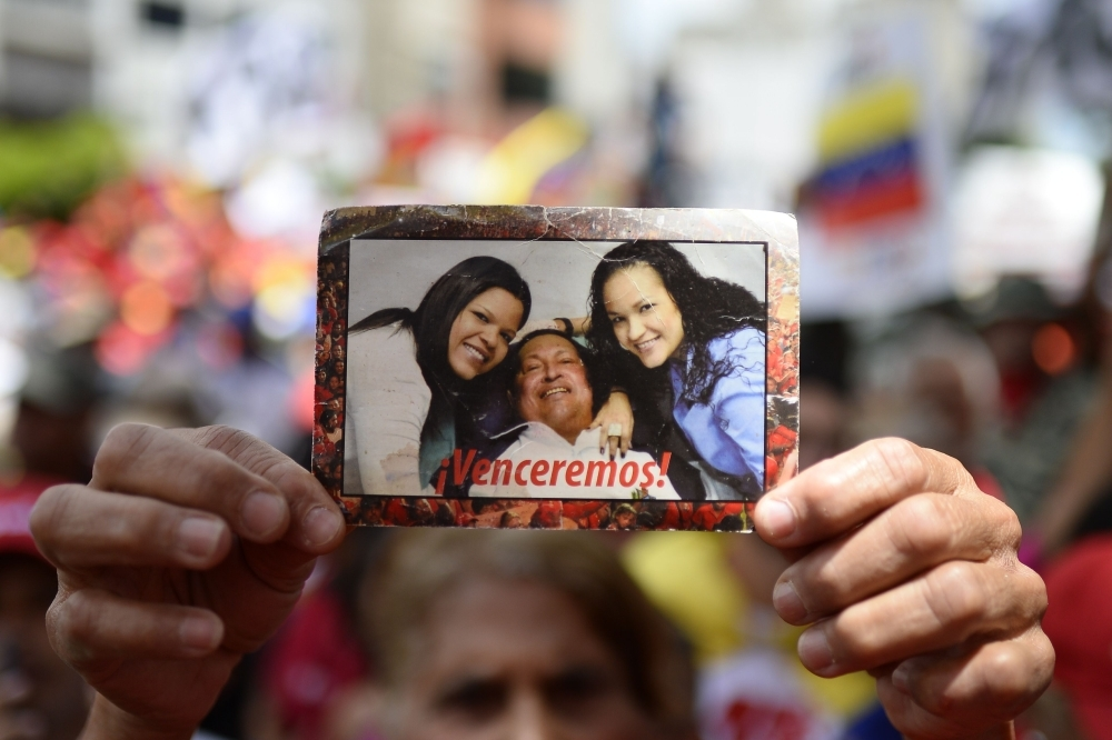 A supporter of Venezuelan President Nicolas Maduro displays a picture of late President Hugo Chavez and his daughters as a lorry carrying boxes with signatures gathered by the government among Venezuelans as part of its