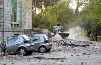 Vehicles are crushes as emergency services workers clear the ruins of a collapsed building roof in Tirana on Saturday, after two earthquakes over 5.0 magnitude struck the Adriatic coastline of Albania. -AFP