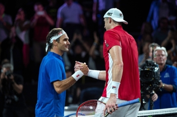 Team Europe's player Roger Federer (L) shakes hands with Team World's player John Isner (R) after winning his match during the 2019 Laver Cup tennis tournament in Geneva, on September 22, 2019. — AFP