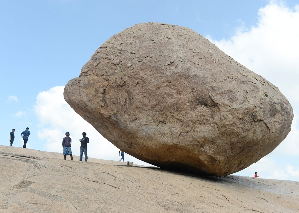 Visitors stand beside the granite boulder 'Krishna's Butterball' at Mahabalipuram on Thursda. The world heritage site of Mahabalipuram could be one of the ports of call for Chinese President Xi Jinping when he holds a summit with his Indian counterpart Narendra Modi reported by Indian media to be held from Oct. 11-13 in the southern state of Tamil Nadu state. — AFP