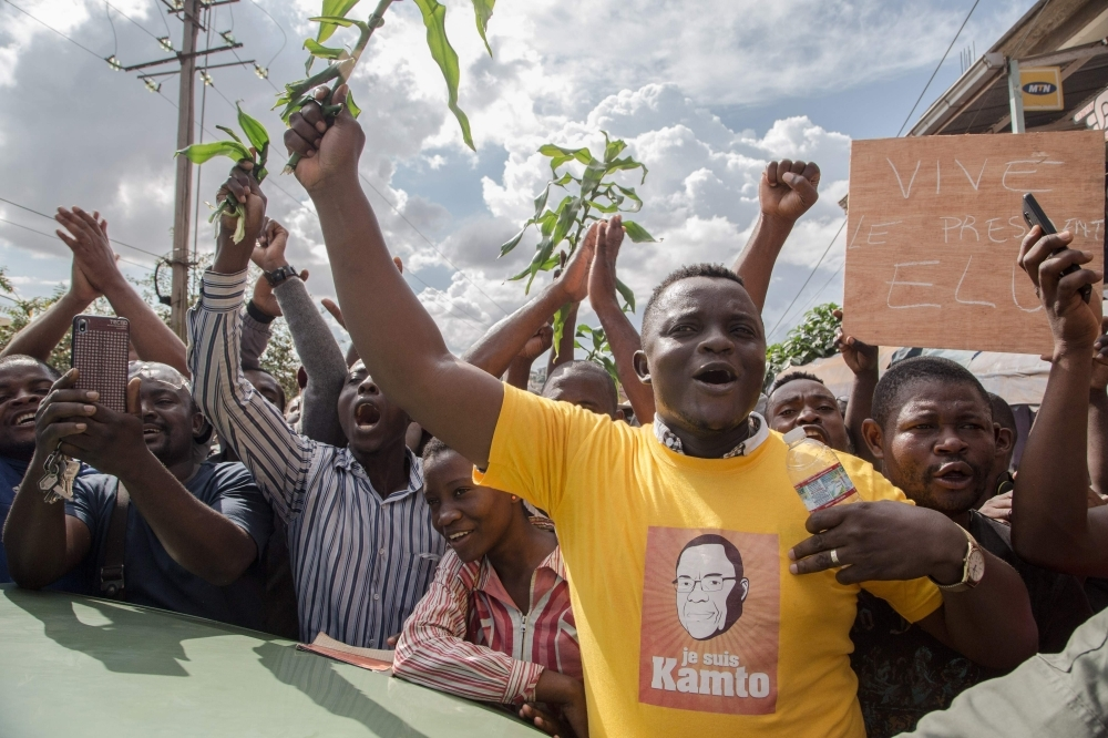 Hundreds of supporters raise their arms while waiting to greet Cameroonian opposition leader Maurice Kamto in Yaounde on Saturday the day of his release from prison. -AFP