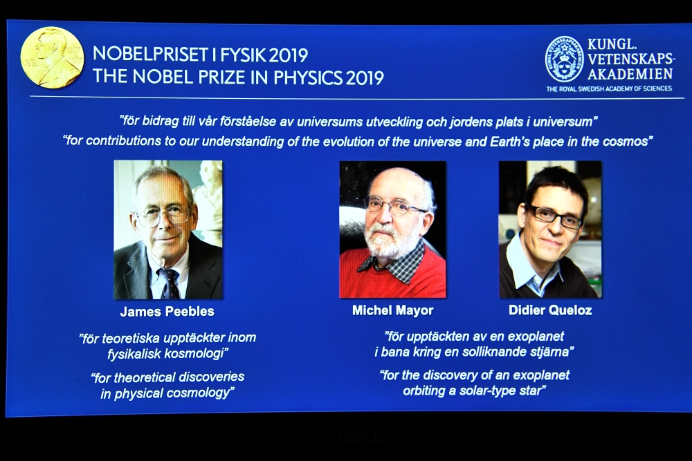 A screen displays the portraits of the laureates of the 2019 Nobel Prize in Physics, James Peebles, left, Michel Mayor, center, and Didier Queloz, during a news conference at the Royal Swedish Academy of Sciences in Stockholm, Sweden, on Tuesday. — Reuters