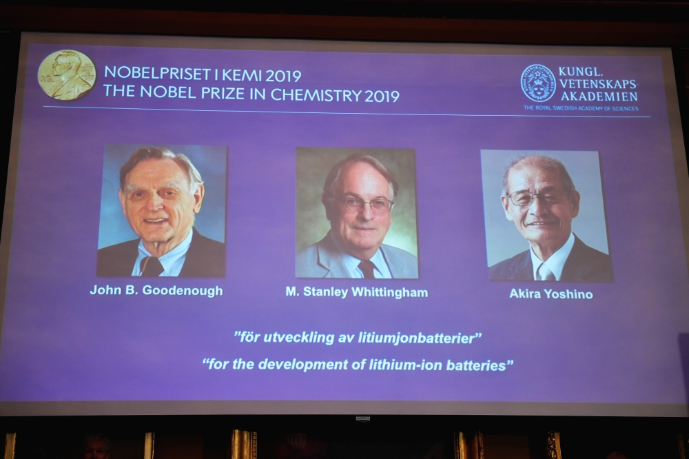 A screen displays the portraits of the laureates of the 2019 Nobel Prize in Chemistry John B. Goodenough, left, M. Stanley Whittingham, center, and Akira Yoshino