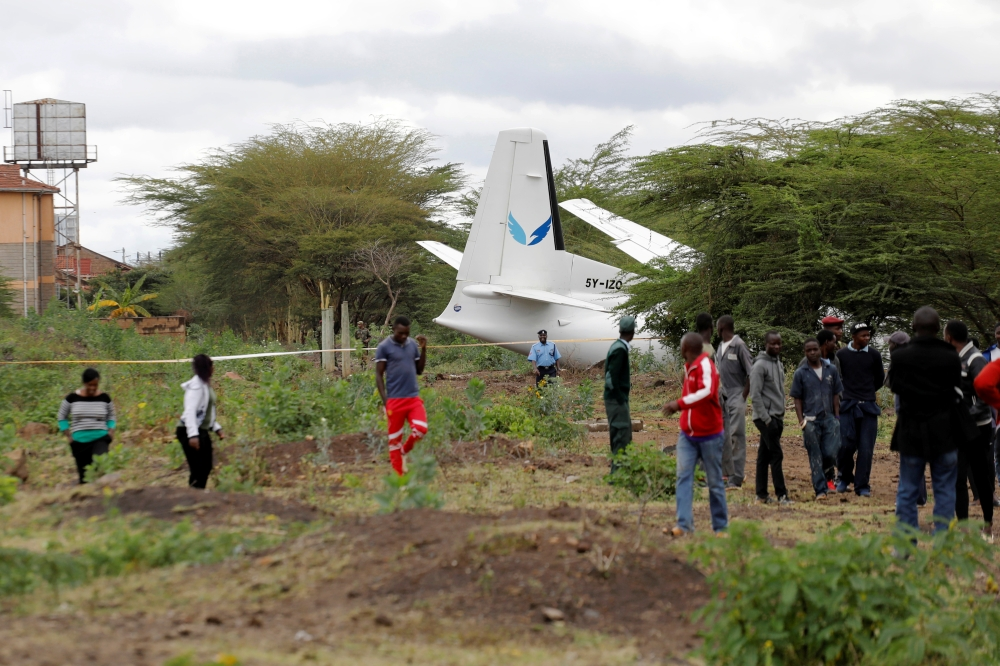 Bystanders watch the Fokker 50, 5Y-IZO plane operated by Silverstone Air that crash landed after take-off from the Wilson Airport in Nairobi, Kenya Friday. — Reuters