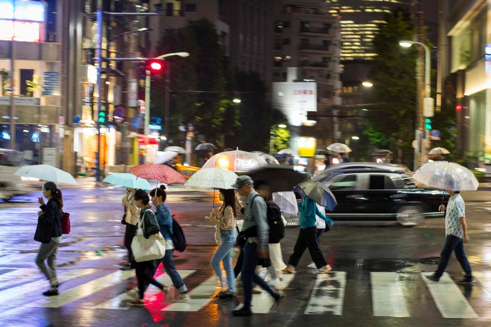 People use umbrellas to shelter from the rain as they cross a street in the Aoyama district of Tokyo on Friday. — AFP