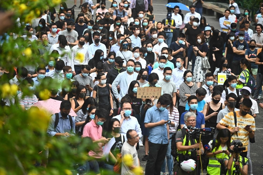 People attend a flash mob rally to show support for pro-democracy protesters in the Central district in Hong Kong on Friday. — AFP