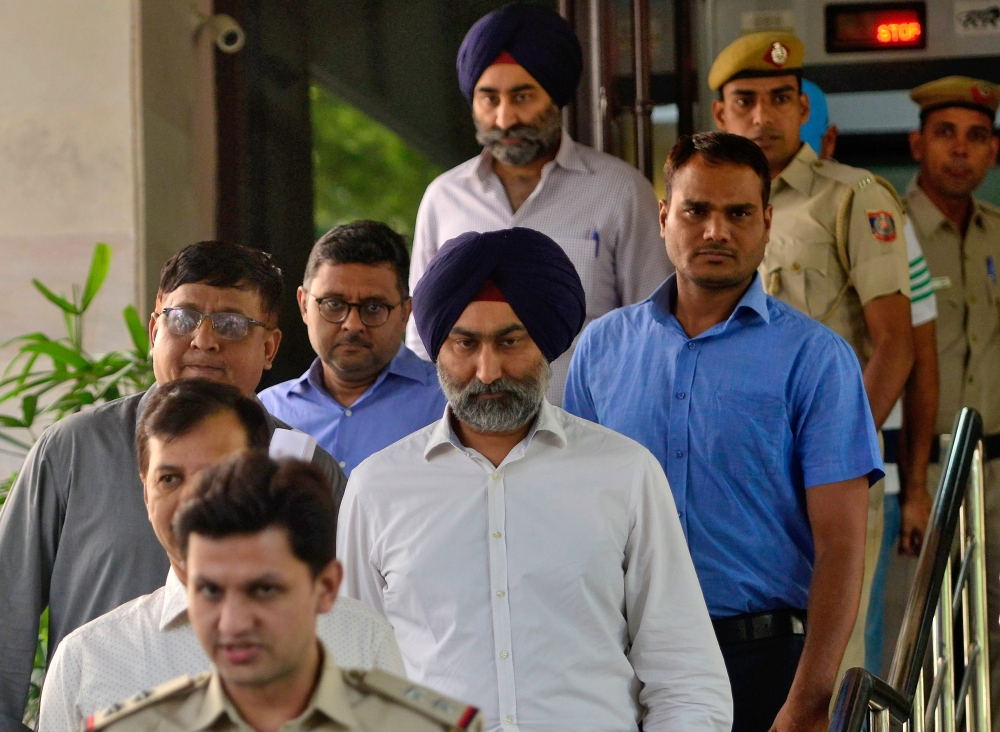 Police escort Malvinder Singh and his brother Shivinder Singh, former directors of Ranbaxy Laboratories, inside a court premises in New Delhi, India, on Friday. — Reuters