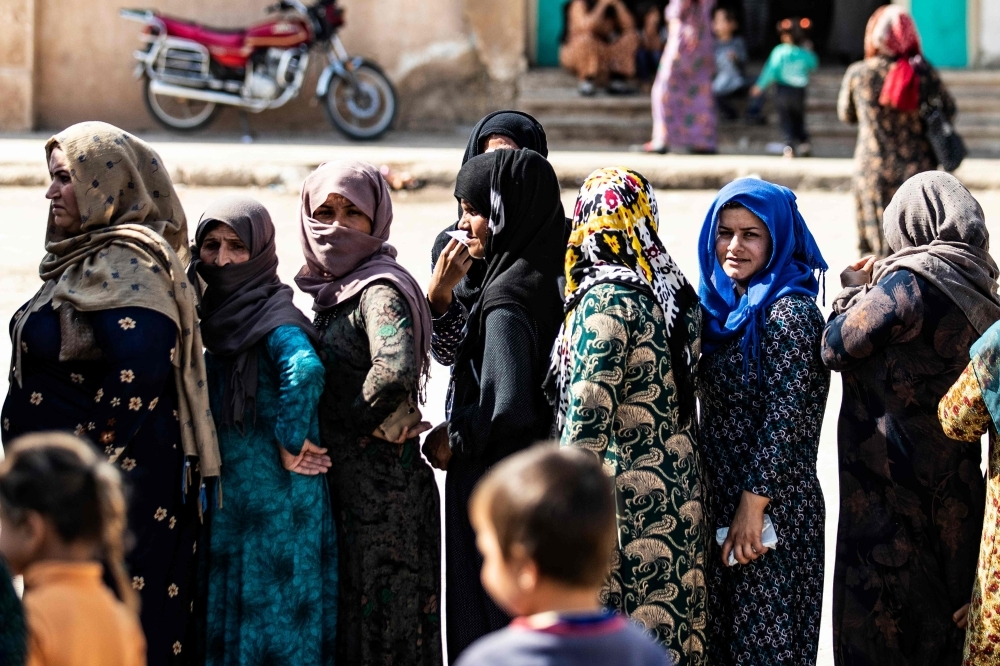 Displaced Syrians, who fled their homes in the border town of Ras al-Ain, receive humanitarian aid on Saturday, in the town of Tal Tamr in the countryside of Syria's northeastern Hasakeh province. Ras Al-Ain would be the first town to fall to Ankara's forces since the launch of its cross-border offensive earlier in the week. Both it and Tal Abyad further west have been major goals of the invasion as Turkey seeks to impose its control over the area between them which although  Kurdish-controlled, is mainly ethnic Arab. — AFP