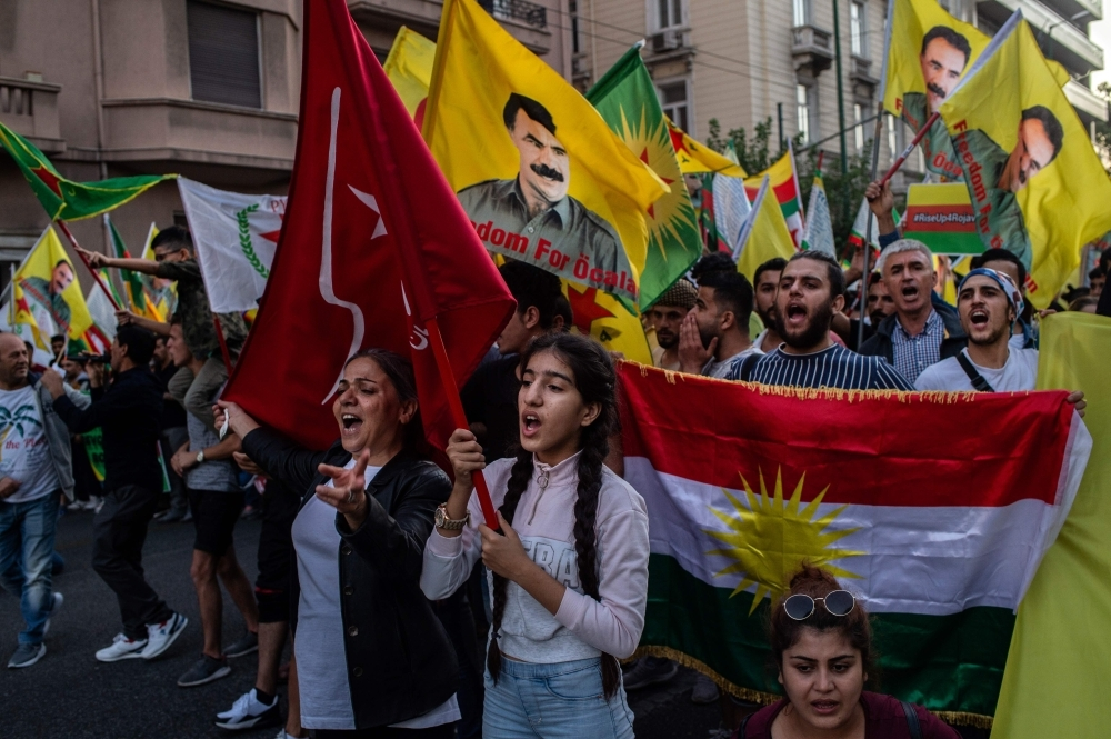 Kurds living in Athens hold kurdish flags and placards during a protest near the Turkish embassy in Athens, on Saturday. -AFP