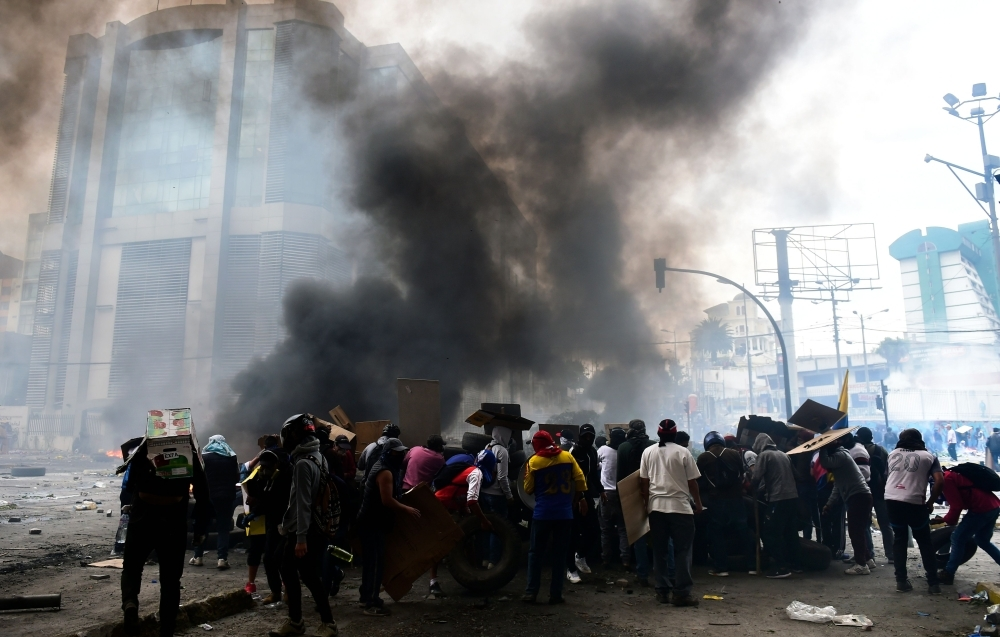 Demonstrators set up barricades during the 10th day of a protest over a fuel price hike ordered by the government to secure an IMF loan, in the surroundings of the National Assembly in Quito on Saturday. -AFP