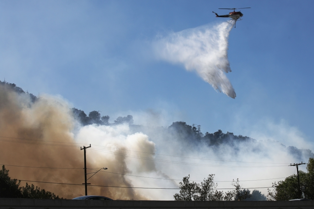 A firefighting helicopter works the Saddleridge Fire on Saturday in Sylmar, California. -AFP
