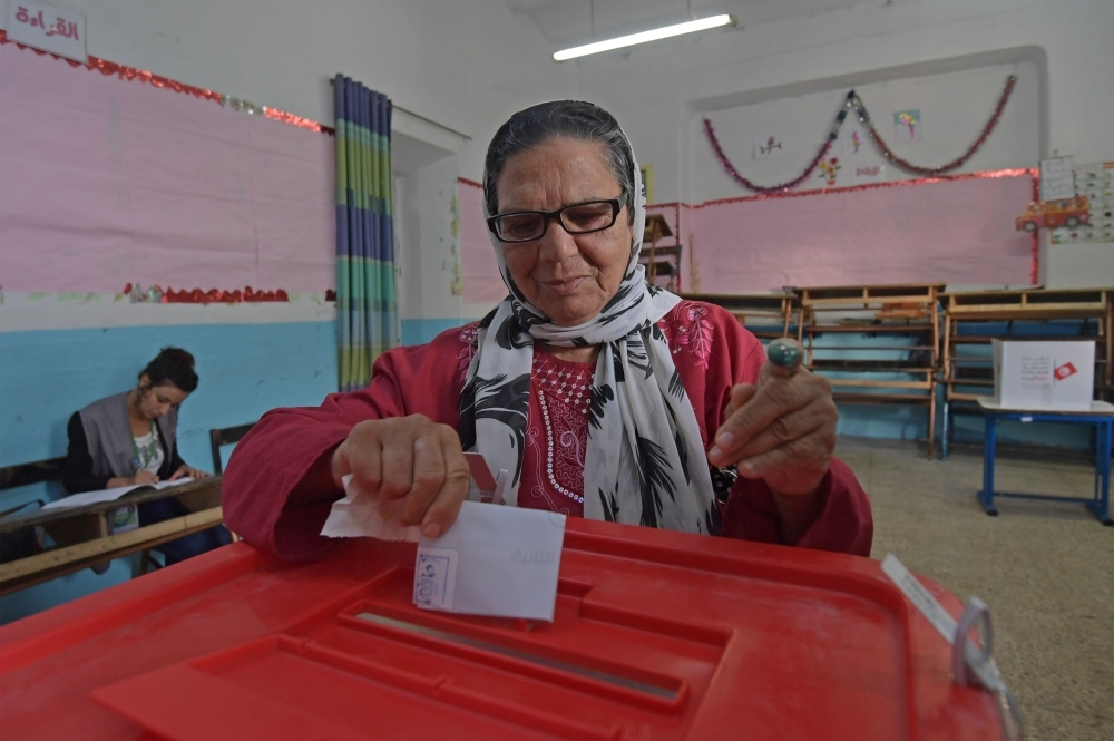 A Tunisian voter casts her ballot at a polling station in the capital Tunis on Sunday during the second round of the presidential election. -AFP