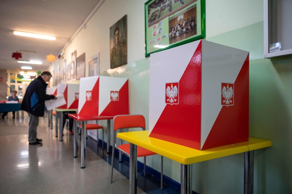 A man is seen at a polling station in Warsaw during the parliamentary elections on Sunday. -AFP