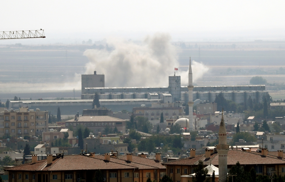 Smoke billows out after Turkish shelling on the Syrian border town of Ras al Ain, as seen from Ceylanpinar, in Sanliurfa province, Turkey, on Sunday. -Reuters