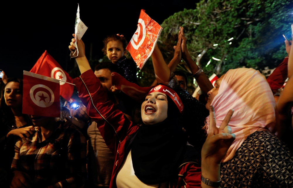 People react after exit poll results were announced in a second round runoff of the presidential election in Tunis, Tunisia, on Sunday. — Reuters