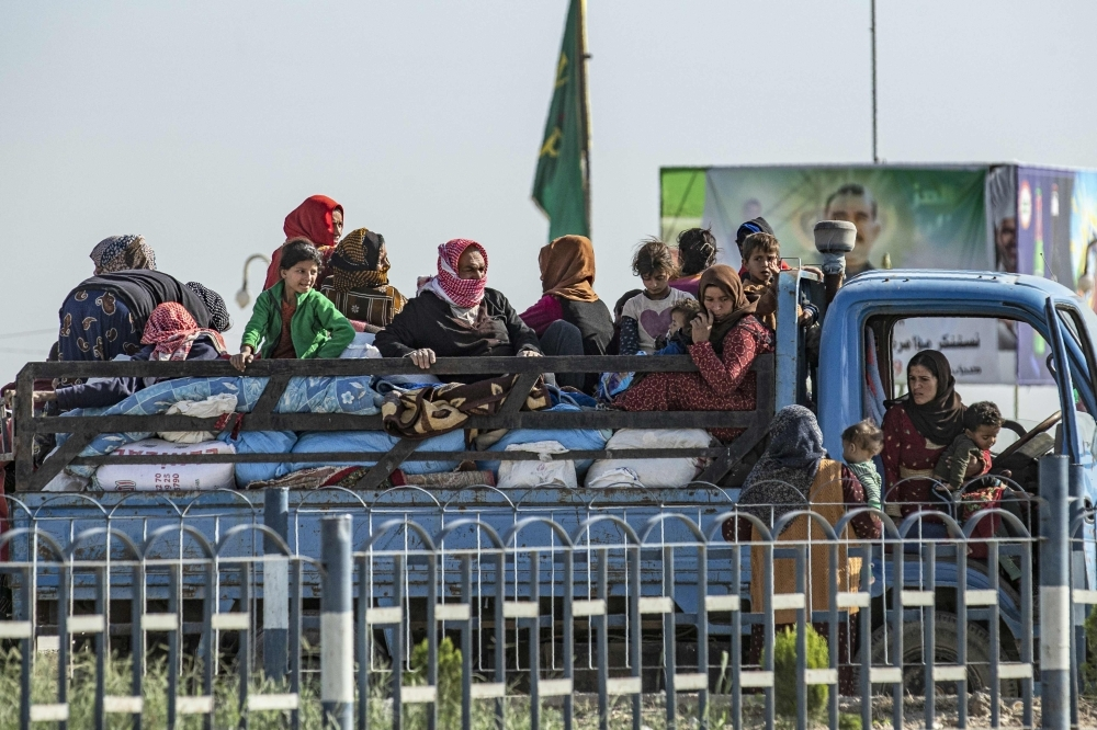 Syrian families fleeing the battle zone between Turkey-led forces and Kurdish fighters from the Syrian Democratic Forces (SDF) in and around the northern flashpoint town of Ras Al-Ain on  the border with Turkey, arrive along with Syrian Arab and Kurdish civilians in the city of Tal Tamr on the outskirts of Hasakeh on Tuesday. — AFP