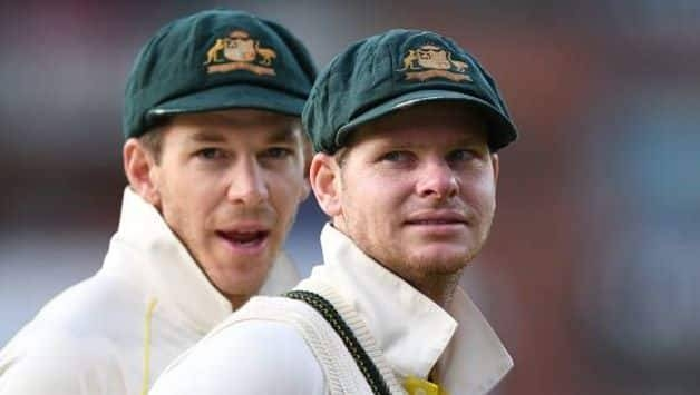 Tim Paine (background) and Steve Smith. — AFP