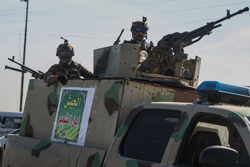 Members of the Iraqi security forces stand guard atop a military vehicle in Karbala near Baghdad on Tuesday. — AFP