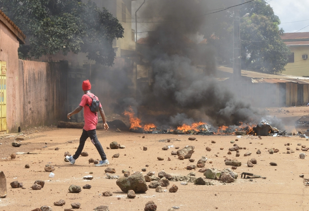 Protesters burn barricades and tires in Conakry street during a demonstration in Guinea on Monday. — AFP