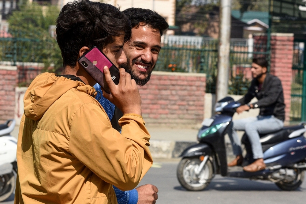 A youth looks on as another one speaks on a mobile phone in Srinagar on Monday, following Indian government's decision to restore mobile phones network in Indian-administered Kashmir. — AFP