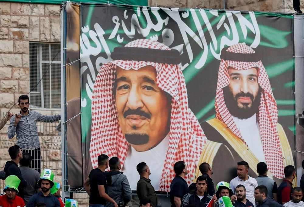 Football fans stand beneath a large banner depicting Saudi Arabia's King Salman (C) and his son Crown Prince Mohammed bin Salman (R) as they attend the World Cup 2022 Asian qualifying match between Palestine and Saudi Arabia in the town of Al-Ram, West Bank, on Tuesday. — AFP