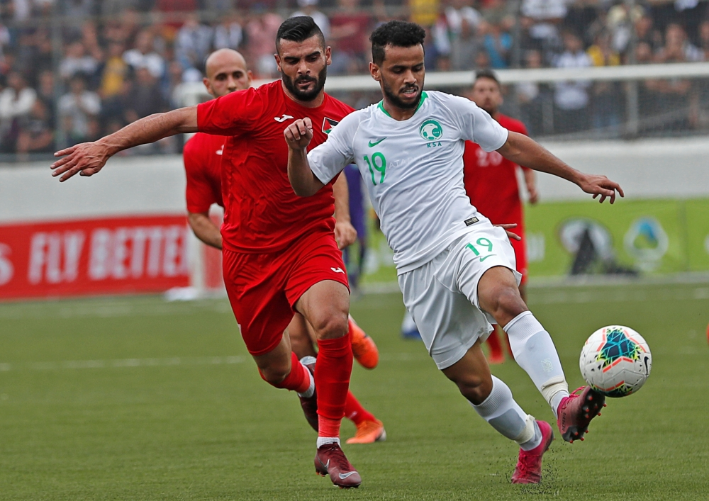 Palestine's Musab Battat in action with Saudi Arabia's Abdulfattah Asiri during the FIFA World Cup 2022 and Asian Cup Qualifier at Faisal Al-Husseini International Stadium, Al-Ram, West Bank, on Wednesday. — Reuters