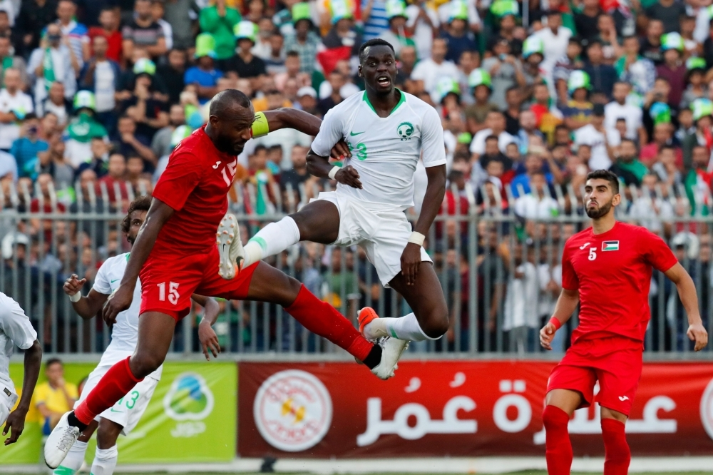 Saudi's defender Ziyad Al-Sahafi vies for the ball with Palestine's defender Abdelatif Bahdari during the World Cup 2022 Asian qualifying match between Palestine and Saudi Arabia in the town of Al-Ram, West Bank, on Wednesday. — AFP