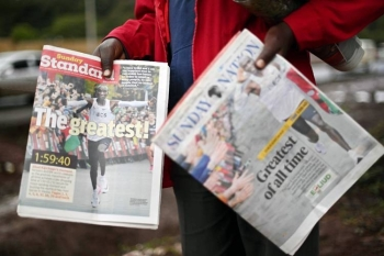 A newspaper vendor sells copies of local daily newspapers featuring Eliud Kipchoge, a Kenyan marathon athlete, in the newspaper headlines in Nairobi on Oct. 13, 2019.  World marathon record holder, Kipchoge, made it into the annals of history on Oct. 12 as the only man to have run a sub-two hour marathon, clocking 1:59:40.2 in the Austrian capital, Vienna at an event organized by British conglomerate Ineos, themed 1:59. — AFP