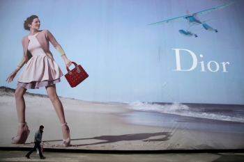 A man walks past a Dior advertisement outside a shopping mall in Wuhan, Hubei province, in this Jan. 19, 2013 file photo. — Reuters