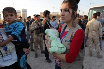 People holding children disembark from a minibus transporting Syrians who have been recently-turned refugees by the Turkish military operation in northeastern Syria upon arriving at the Bardarash camp, near the Kurdish city of Dohuk, in Iraq's autonomous Kurdish region, on Wednesday. — AFP