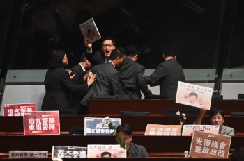 Members of security try to block pro-democracy lawmaker Lam Cheuk-ting, center-facing, as he chants slogans in protest as Hong Kong Chief Executive Carrie Lam, not pictured, holds a question and answer session at the Legislative Council (Legco) in Hong Kong on Thursday. — AFP
