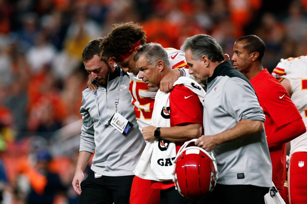 Kansas City Chiefs quarterback Patrick Mahomes (15) is helped off the field after a play in the second quarter against the Denver Broncos at Empower Field at Mile High. — Reuters