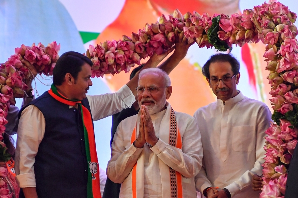 India's Prime Minister Narendra Modi, center, is being garlanded by Hindu right-wing party Shiv Sena Chief Uddhav Thackeray, right, and Chief Minister of the state Devendra Fadnavis, left, as they attend a public rally in the run up to the Maharashtra state assembly elections, in Mumbai on Friday. — AFP