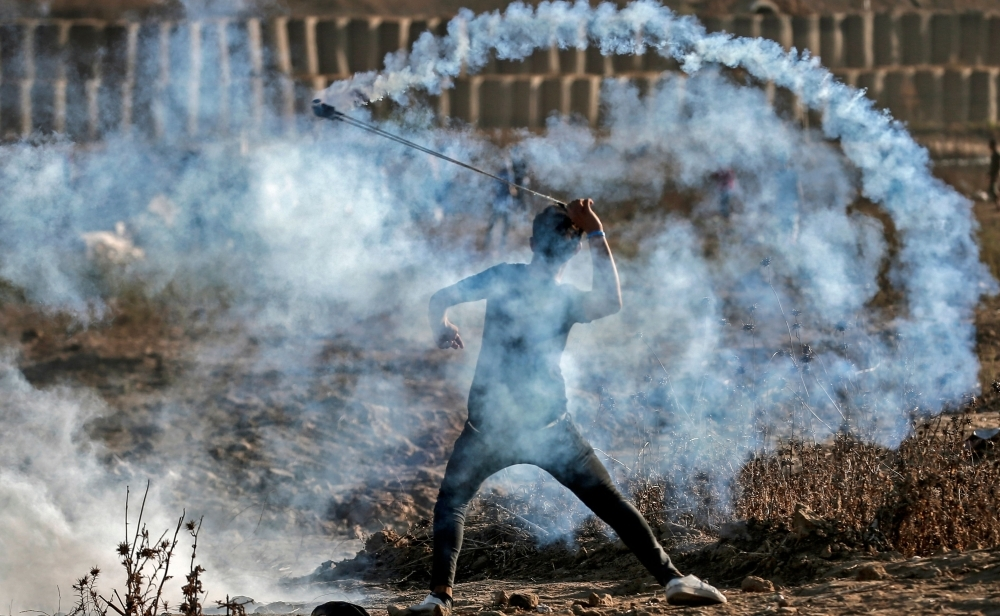 A Palestinian protester uses a slingshot to throw back a tear gas canister at Israeli forces amidst clashes during a demonstration along the border with Israel east of Bureij in the central Gaza Strip on Friday. — AFP