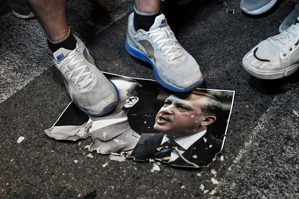 Protesters step on a paper depicting a combination of pictures of Turkish President Recep Tayyip Erdogan, right, and leader of the Nazi Party, Adolf Hitler, left, during a demonstration outside the US embassy in Athens on Thursday to protest against Turkish offensive against Syria's Kurdish forces and the stance of its NATO allies. — AFP