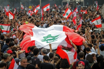 Lebanese demonstrators wave the national flag during a protest against dire economic conditions in downtown Beirut on Friday. — AFP
