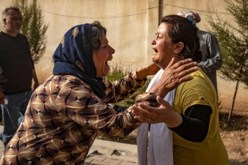 Women react as the body of a man killed during Turkish shelling in the area surrounding the Syrian Kurdish town of Ras Al-Ain arrives at a hospital in the nearby town of Tal Tamr following the announced cease-fire on Friday. — AFP